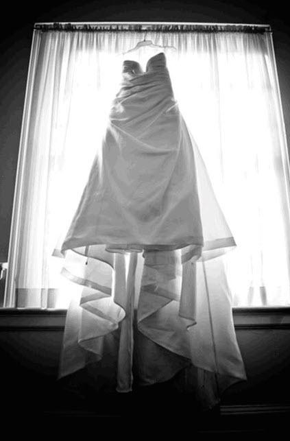 black-and-white-artistic-wedding-photos-groom-in-tux-white-wedding-dress-hangs-in-window.original.jpg